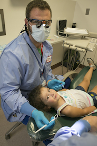 Photo of School of Dental Medicine team member and child at Give Kids a Smile event