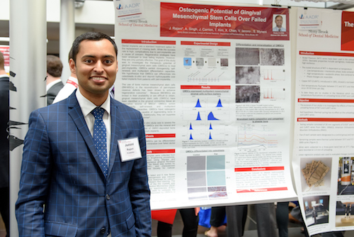 "Junaid Rajani presents his research poster, ""Osteogenic Potential of Gingival Mesenchymal Stem Cells Over Failed Implants."""