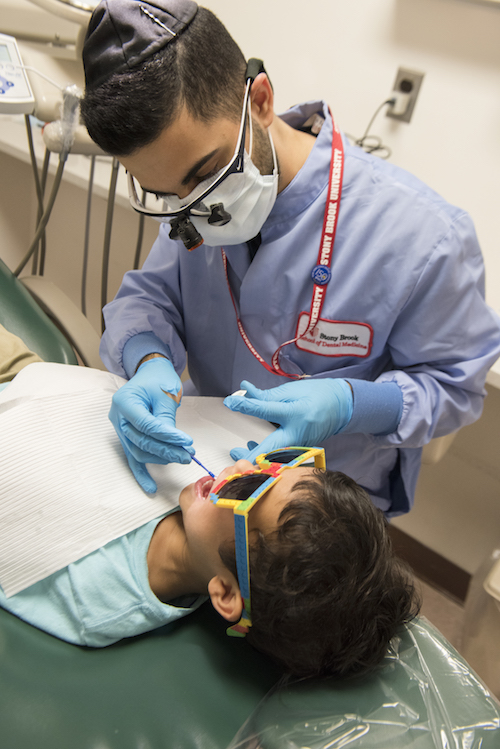 Stony Brook School of Dental Medicine Student Provides Free Dental Services to Child at Give Kids A Smile Day Event