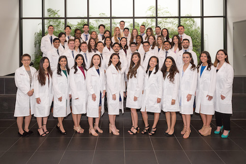 Group photo of Stony Brook School of Dental Medicine's Class of 2022 in their white coats.