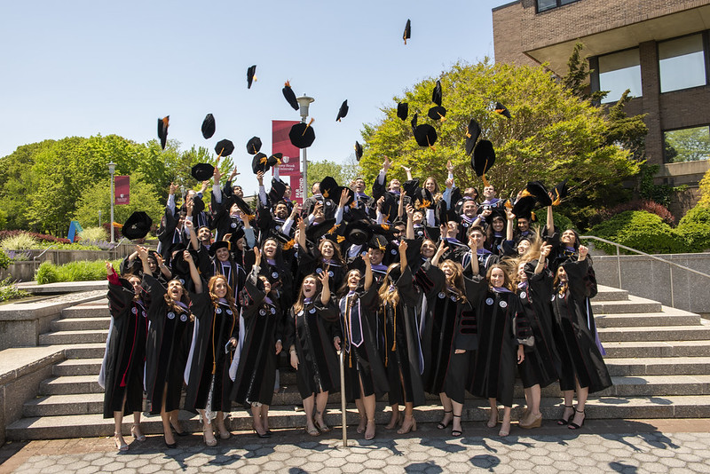 An outdoor group photo of Stony Brook School of Dental Medicine graduates in regalia tossing their graduation caps. They are standing on steps with trees in the background.