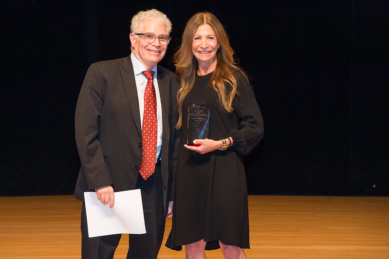 Dr. Ralph Epstein (left) and Dr. Stacy Reisfeld (right) on stage at the Staller Center for the Arts. Dr. Stacy Reisfeld holds an award to present to Dr. Epstein.