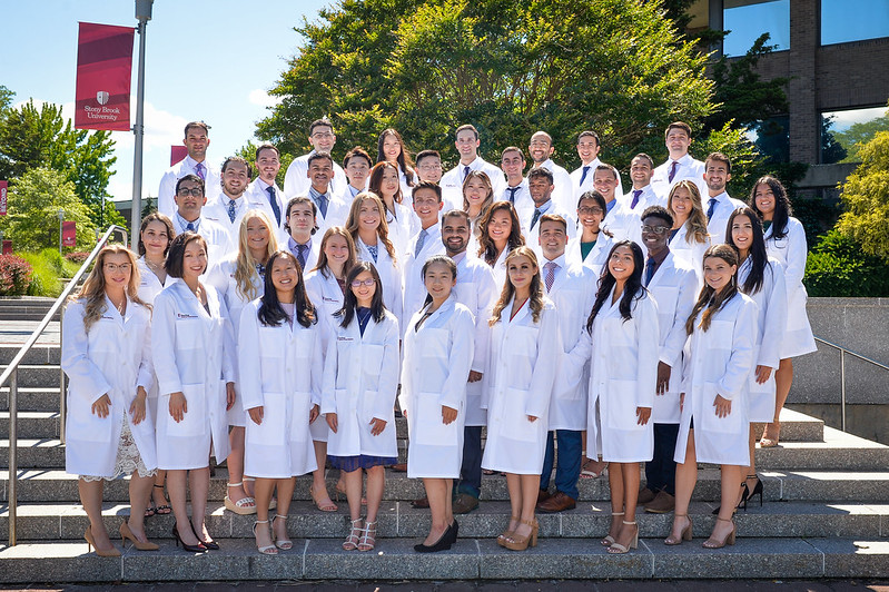 An outdoor group photo of 43 Stony Brook School of Dental Medicine students donning clinical white coats at Stony Brook University.