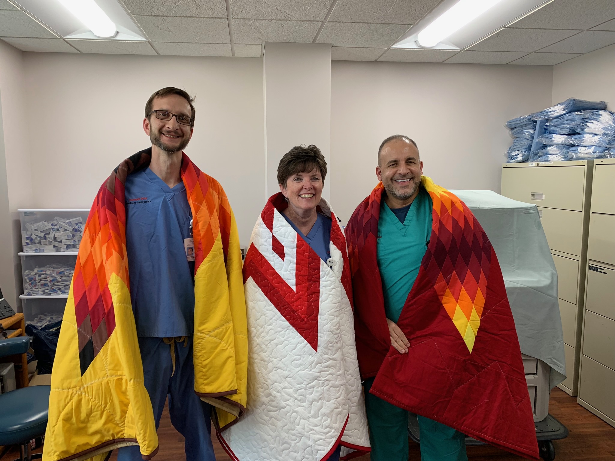 Christopher Noga, Dr. Mary Truhlar, and Dr. John Foti wrapped in star quilts presented by the Oglala Lakota Sioux tribe.