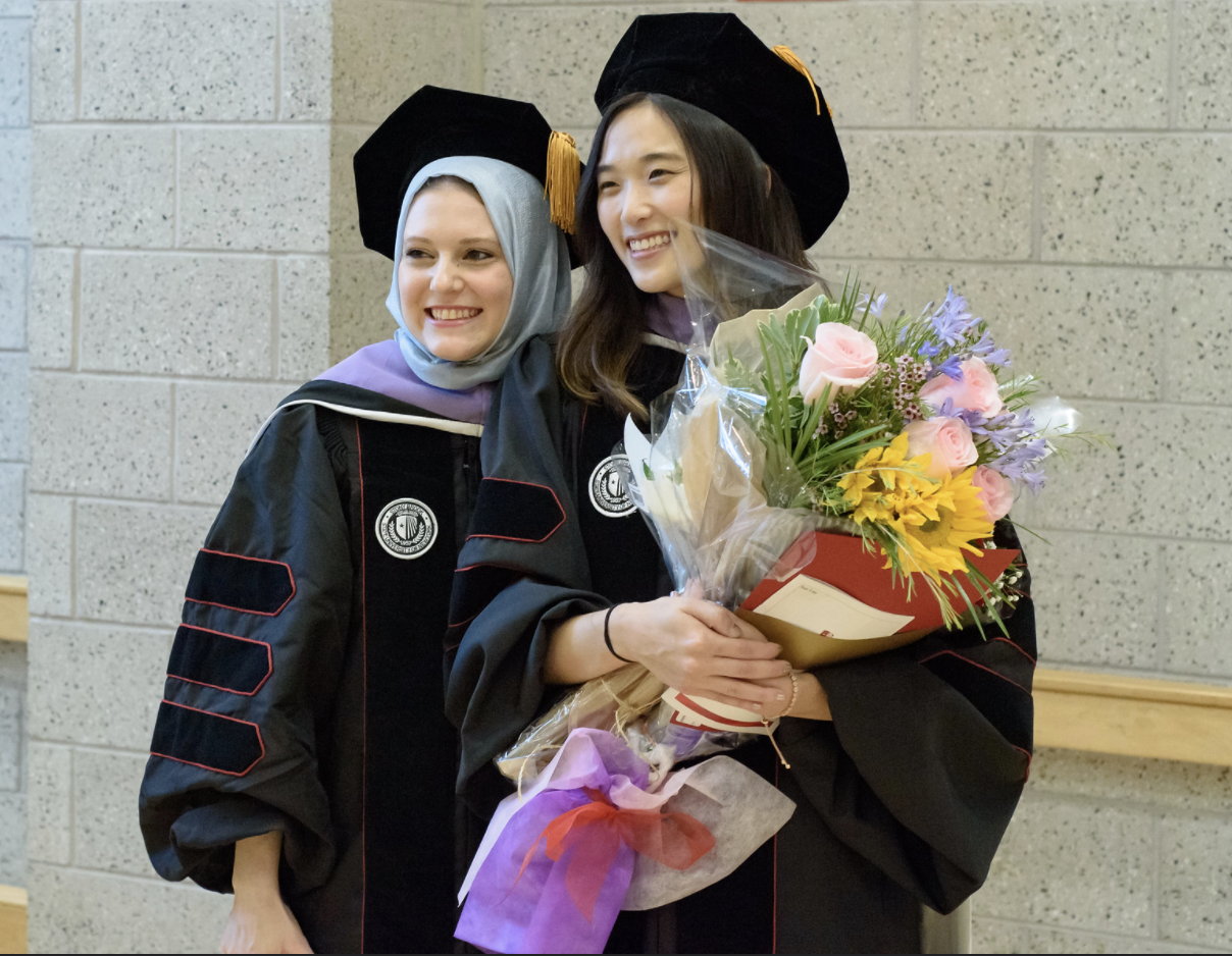 Two Class of 2019 students pose following the 43rd annual Commencement Ceremony of Stony Brook University School of Dental Medicine