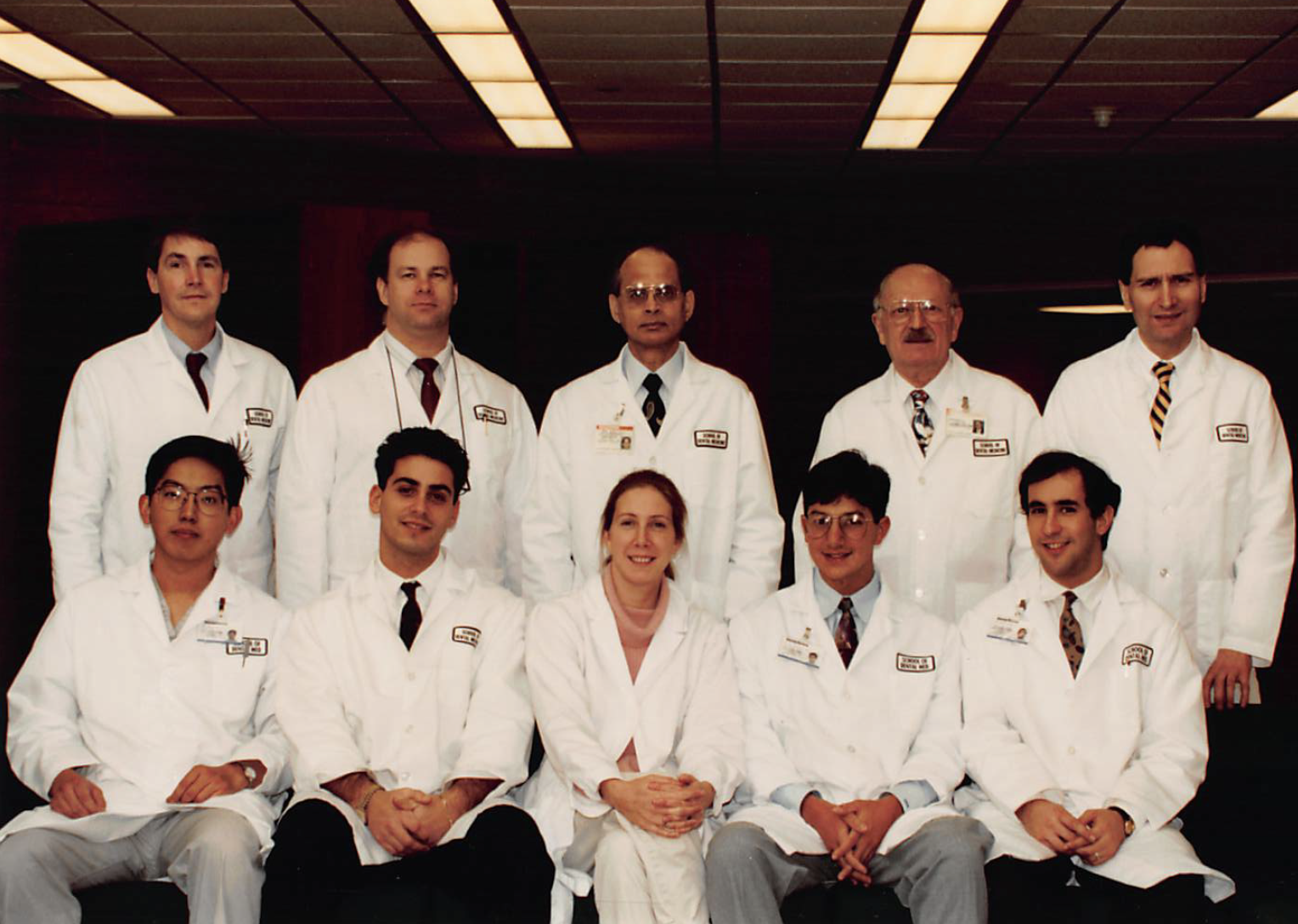 A group photo with one row of people standing and another row sitting in front. Everyone is wearing a white lab coat. In the photo are members of the original class of Stony Brook School of Dental Medicine's advanced education program in periodontics.