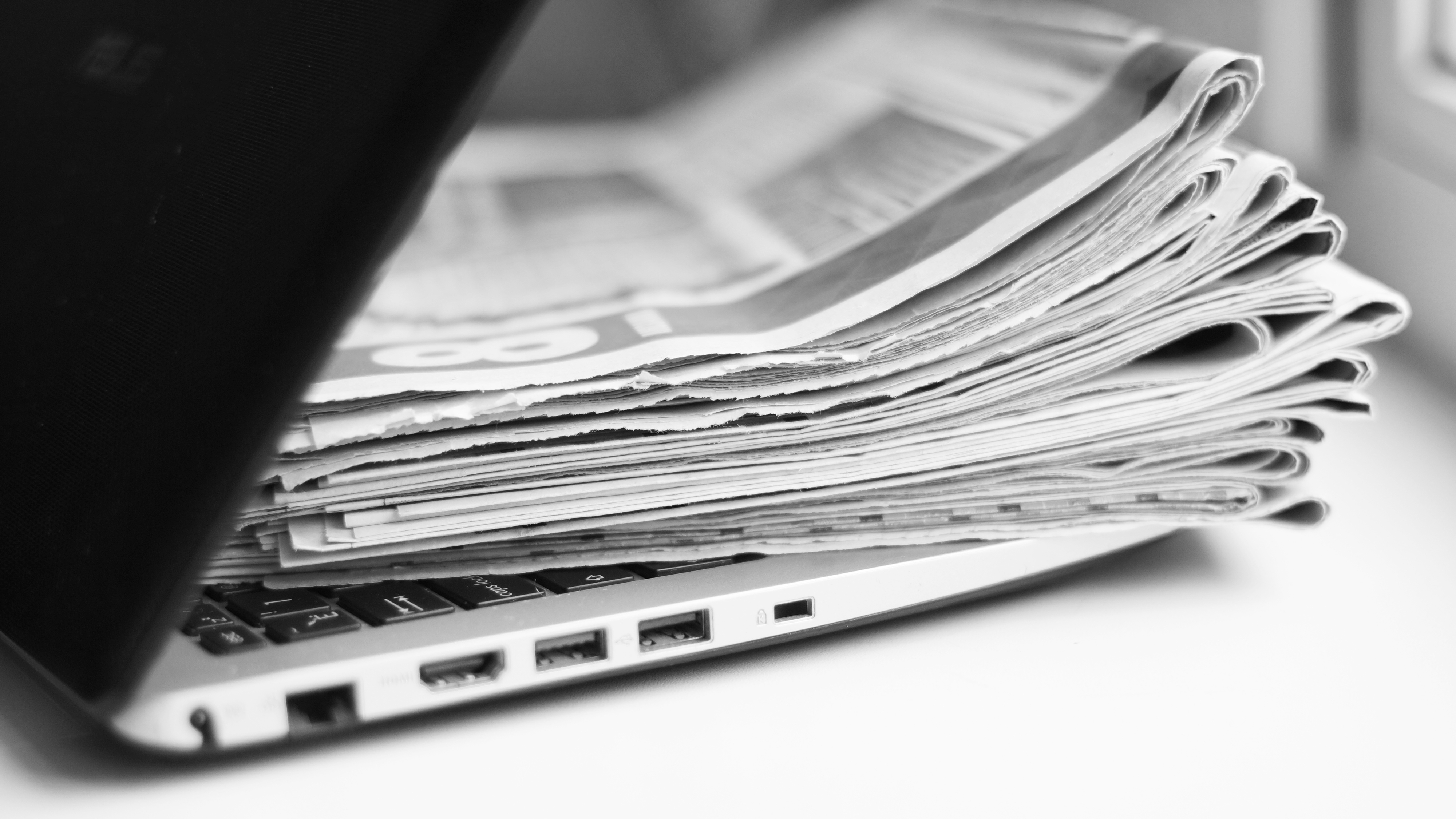 Newspapers within a closing laptop