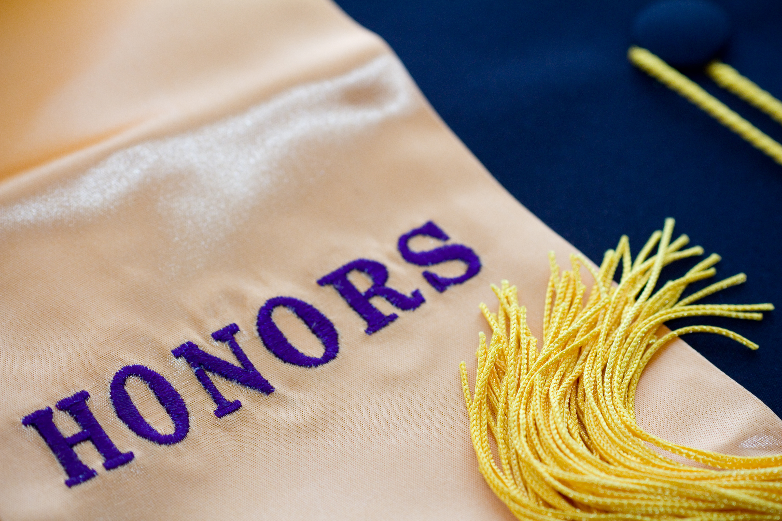 """""""HONORS"""" written on a graduation stole with a yellow tassel laid over the fabric."""