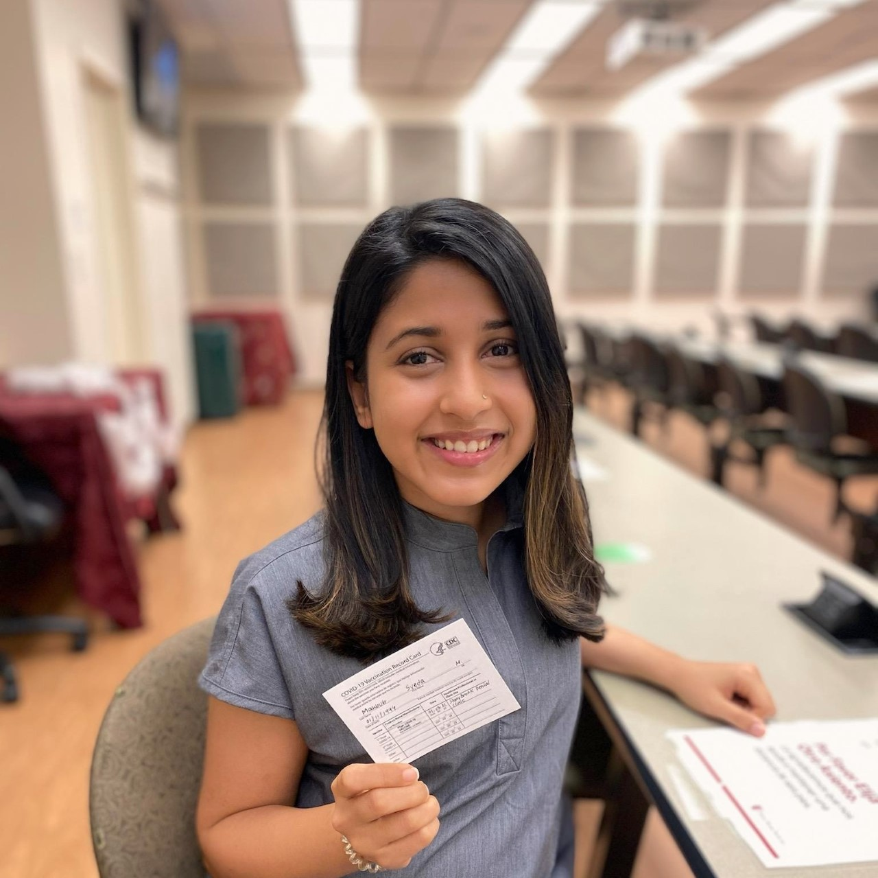 Stony Brook School of Dental Medicine student displays proof of vaccine card.