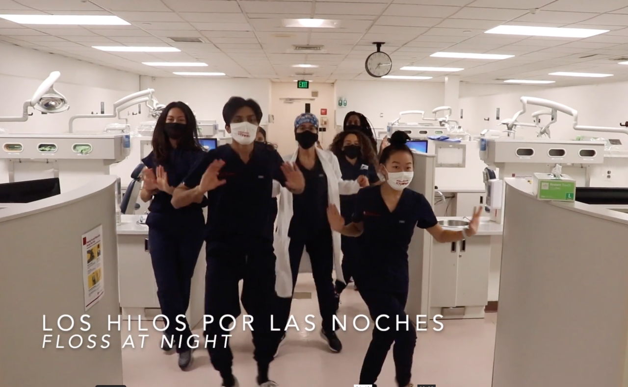 Screen shot from video of Stony Brook School of Dental Medicine students dancing in scrubs in the dental clinic.