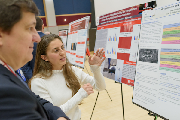 Student Heather Ercolano explains her research to Dr. Wellington Rody at the Stony Brook University School of Dental Medicine's 2019 Leo and Mickey Sreebny Lectureship and School of Dental Medicine Research Symposium
