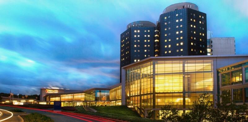 Photo Stony Brook University Hospital lit up at night with dark sky behind it